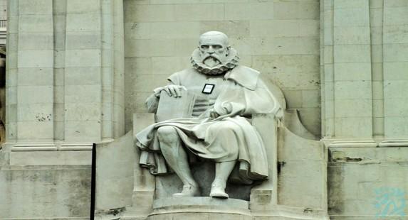 塞外提斯是西班牙最伟大的作家他右手拿着他的名著唐吉诃德左臂在战争中失去雕刻家巧妙地用披风掩盖起来